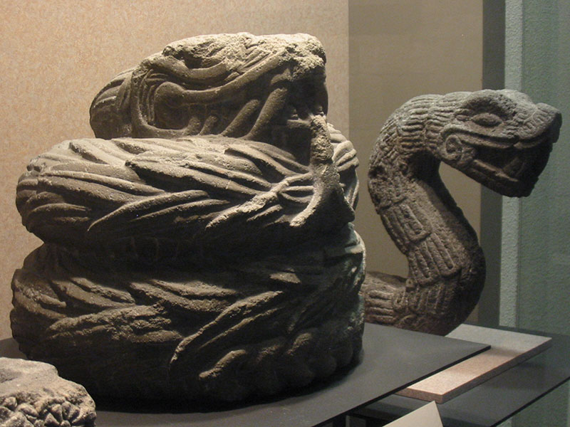 Stone sculptures of feathered serpents. Photo by Thelmadatter via Wikimedia Commons.
