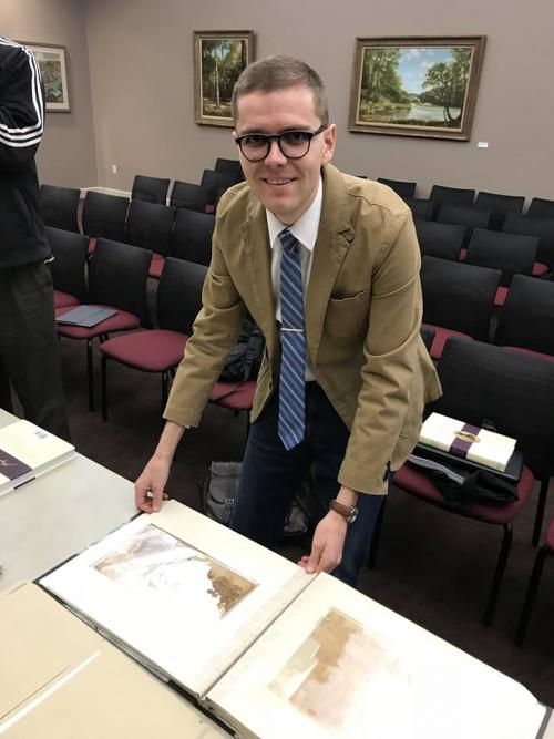 Book of Mormon Central research associate Stephen O. Smoot poses with Joseph Smith's Egyptian papyri.