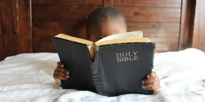 Child reading the bible. Image via pixabay