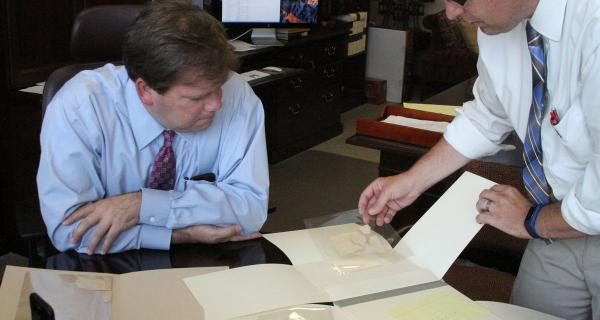 Reid Neilson, left, Assistant Church Historian and Recorder, and Robin Scott Jensen, associate managing historian and project archivist for the Joseph Papers project, go over portions of the original manuscript of the Book of Mormon that have been in the